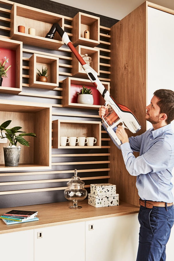 Man vacuuming above a piece of furniture